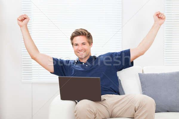 Podniecony człowiek laptop ręce portret sofa Zdjęcia stock © AndreyPopov