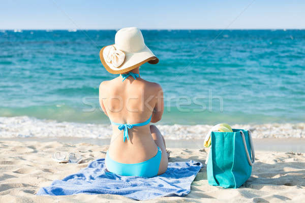 Woman in bikini relaxing on beach towel enjoying the ocean view Stock photo © AndreyPopov