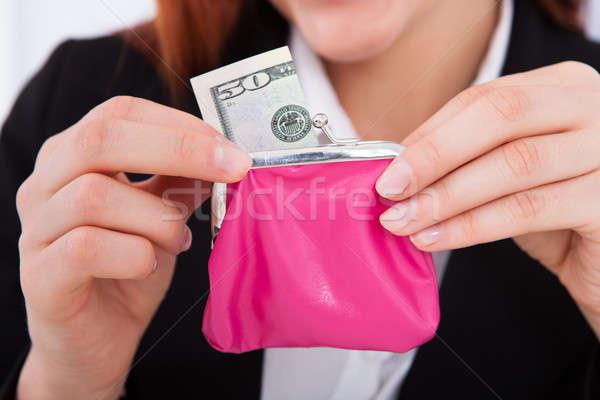 Businesswoman Putting 50 Dollar Bill In Purse Stock photo © AndreyPopov