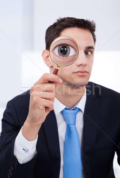 Imprenditore guardando lente di ingrandimento ritratto ufficio business Foto d'archivio © AndreyPopov