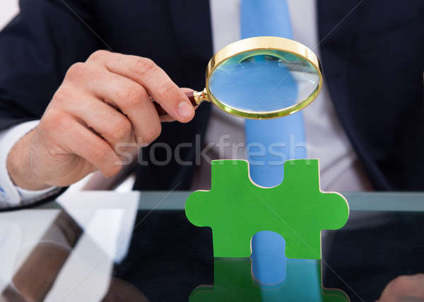 Businessman Scrutinizing Puzzle Piece With Magnifying Glass Stock photo © AndreyPopov
