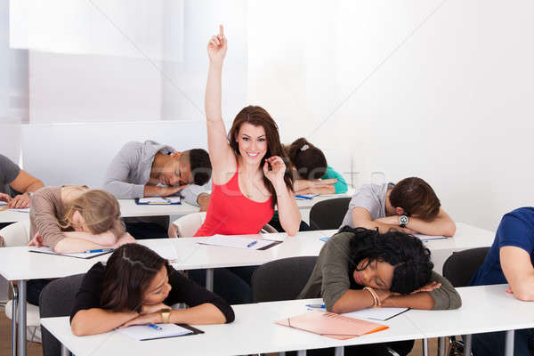 Smiling Student Raising Hand With Classmates Sleeping At Desk Stock photo © AndreyPopov