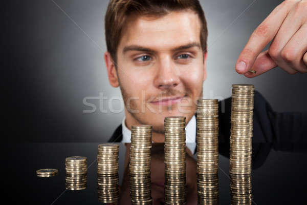 Young Businessman Stacking Coins At Desk Stock photo © AndreyPopov