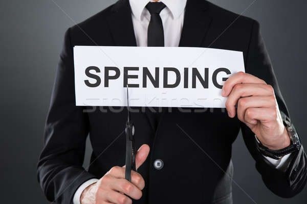 Businessman Cutting The Word Spending On Paper With Scissors Stock photo © AndreyPopov