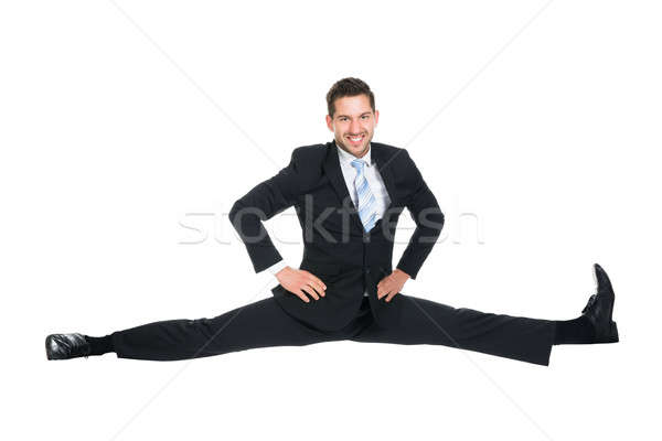 Businessman Doing Splits Over White Background Stock photo © AndreyPopov