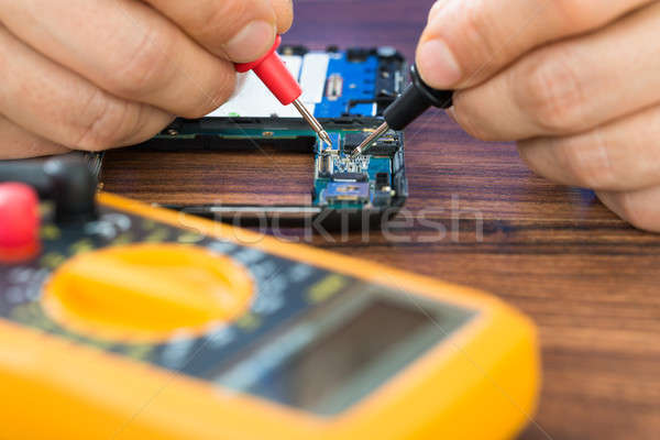 Human Hand  Repairing Cellphone With Multimeter Stock photo © AndreyPopov