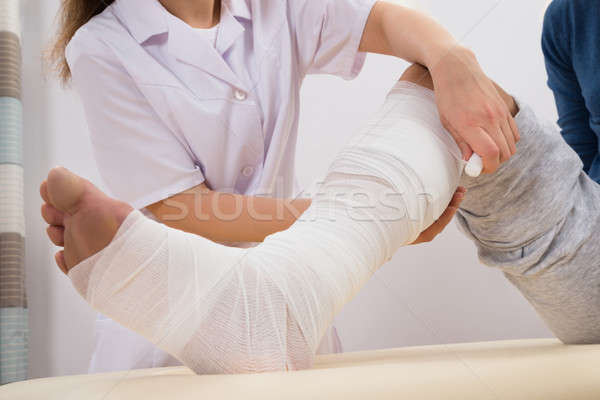 Doctor Bandaging Patient's Leg Stock photo © AndreyPopov