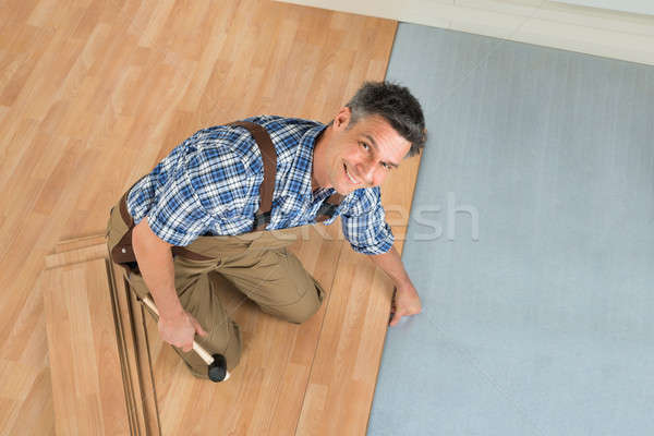 Stock photo: Happy Worker Assembling New Laminate Floor