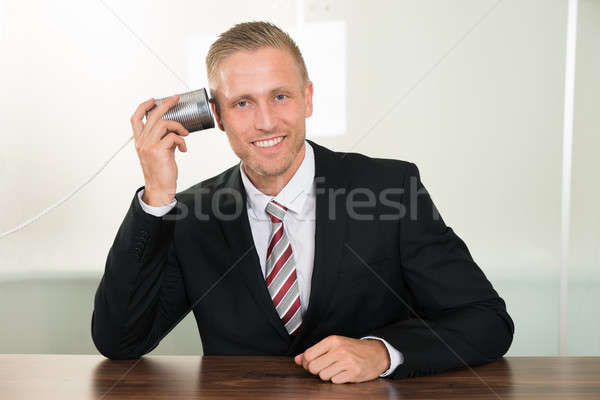 Businessman Listening From Tin Cans Phone Stock photo © AndreyPopov