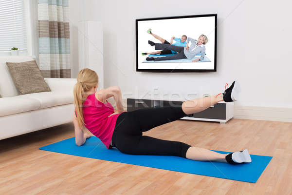 Woman Exercising On Exercise Mat In Front Of Television Stock photo © AndreyPopov