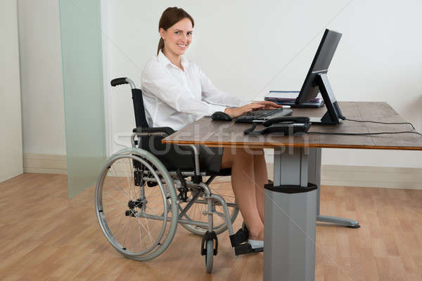 Businesswoman On Wheelchair While Working On Computer Stock photo © AndreyPopov