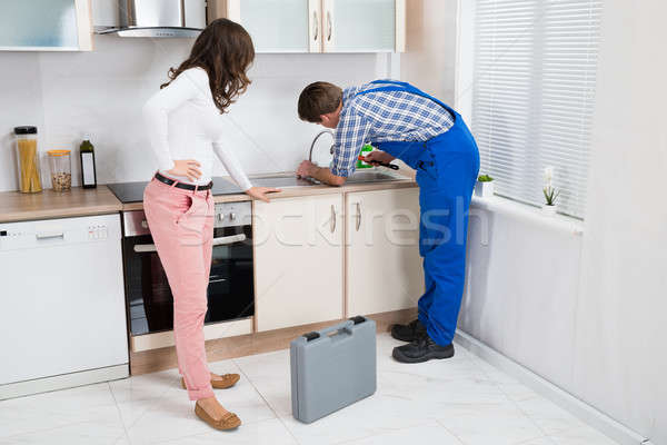 Woman Looking At Plumber Fixing Sink Stock photo © AndreyPopov