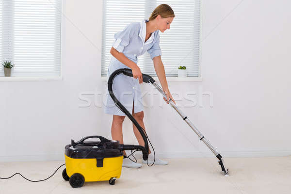 Female Maid Cleaning With Vacuum Cleaner Stock photo © AndreyPopov