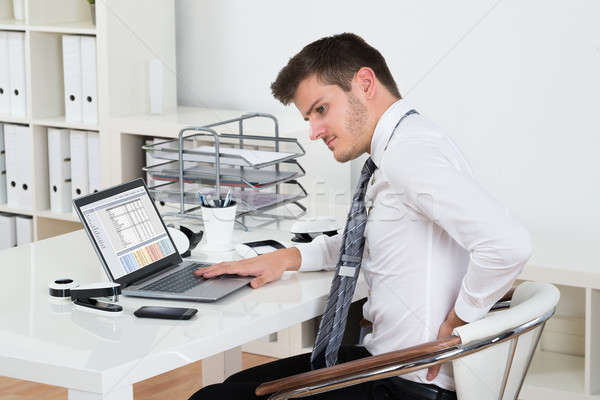 Businessman Suffering From Backpain In Office Stock photo © AndreyPopov