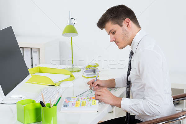 Businessman Working On Gantt Chart At Desk Stock photo © AndreyPopov