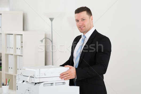 Confident Businessman Standing By Photocopy Machine Stock photo © AndreyPopov