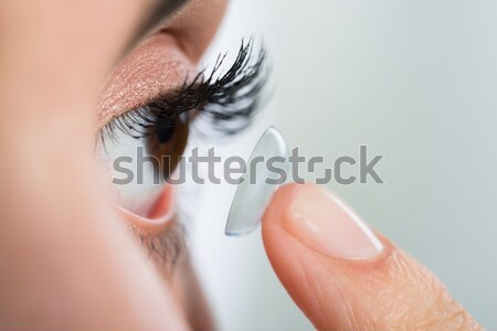 Woman Wearing Contact Lens At Home Stock photo © AndreyPopov