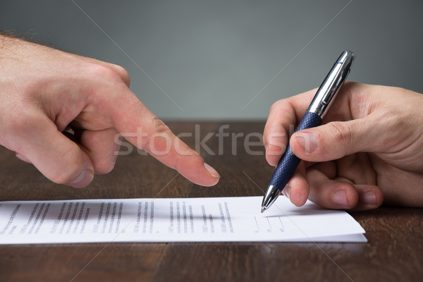 Businessman Pointing Partner To Sign Agreement At Desk Stock photo © AndreyPopov
