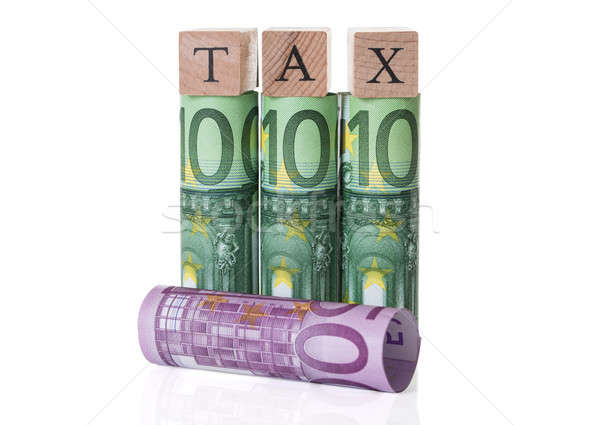 Stock photo: Tax Blocks Arranged On Rolled Euro Notes