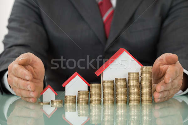 Businessman With Different Houses And Stacks Of Coins Stock photo © AndreyPopov