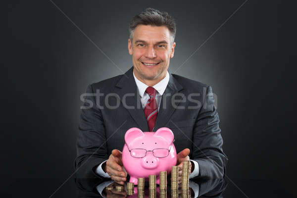 Businessman Sheltering Coins And Piggybank At Desk Stock photo © AndreyPopov
