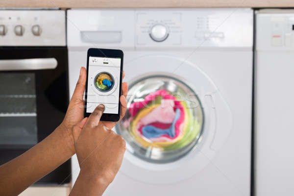Woman's Hand Operating Washing Machine With Mobile Phone Stock photo © AndreyPopov