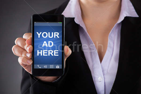 Person Holding Mobile Phone Showing Your Ad Here Text Stock photo © AndreyPopov
