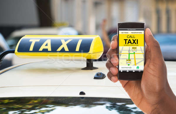 Person Booking Taxi On Mobile Phone Stock photo © AndreyPopov
