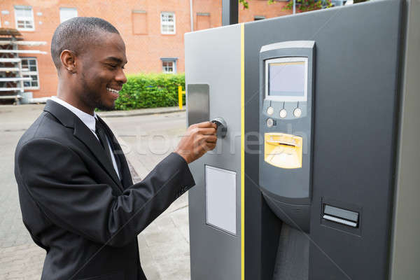 Businessman Inserting Coin Into Parking Meter Stock photo © AndreyPopov