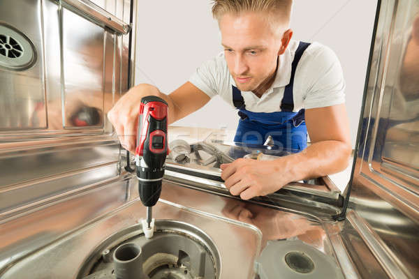 Man Repairing Dishwasher With Electric Drill Stock photo © AndreyPopov