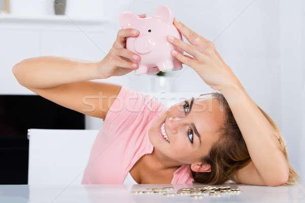 Happy Woman Emptying Her Piggybank Savings Stock photo © AndreyPopov
