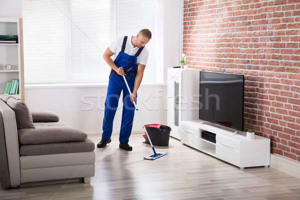 Male Janitor Sweeping Floor At Home Stock photo © AndreyPopov