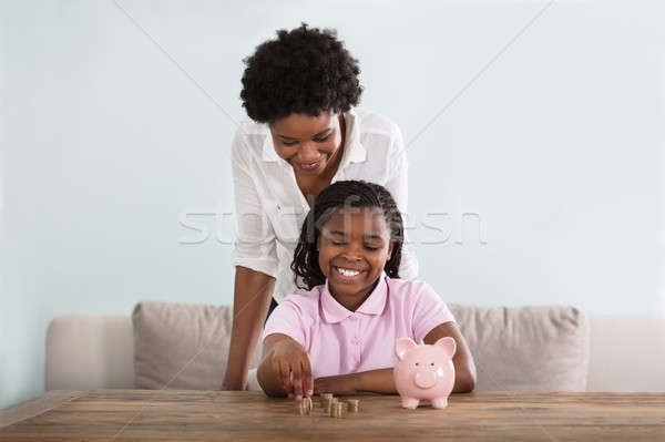 Girl With Mother Inserting Coins In Piggy Bank Stock photo © AndreyPopov