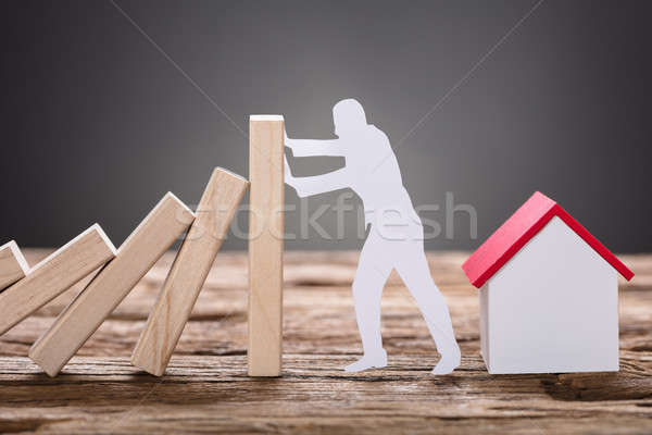 Paper Man Stopping Wooden Domino Blocks By Model Home Stock photo © AndreyPopov