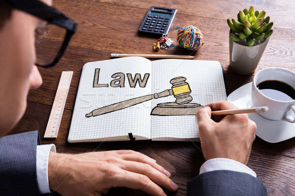 Lawyer Drawing Law Concept In Book At Desk Stock photo © AndreyPopov