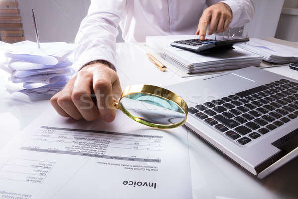 Stock photo: Auditor Checking Invoice Using Magnifying Glass