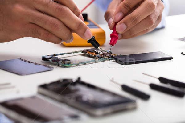 Technician Examining Mobile Phone With Digital Multimeter Stock photo © AndreyPopov