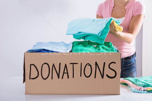 Woman Putting Clothes Inside Donation Box Stock photo © AndreyPopov