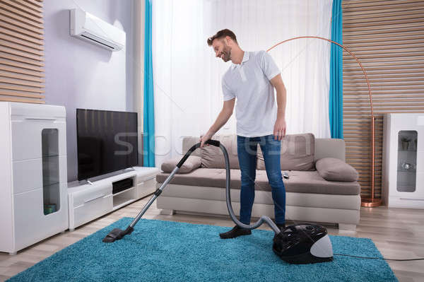 Man Cleaning Carpet With Vacuum Cleaner Stock photo © AndreyPopov