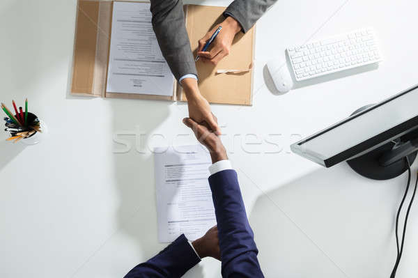 Businessperson Shaking Hand With Candidate Over White Desk Stock photo © AndreyPopov