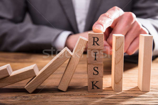 Businessperson's Finger Stopping Dominos From Falling Stock photo © AndreyPopov