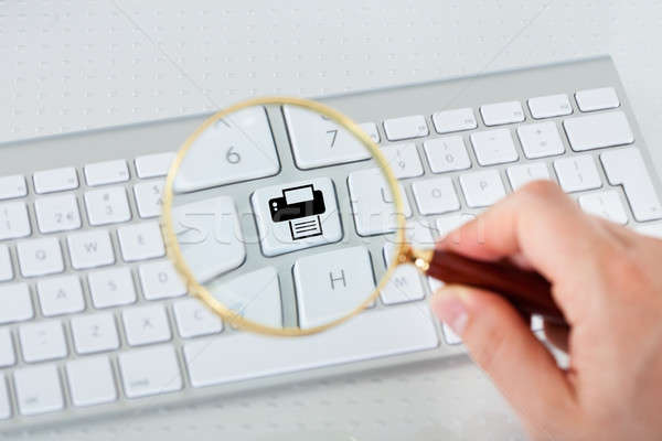 Looking at printer key through magnifying glass Stock photo © AndreyPopov