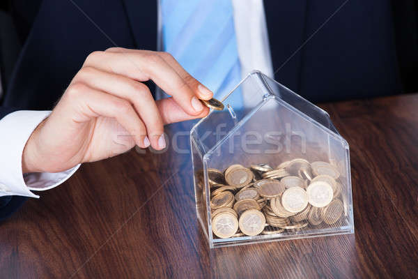 Businessman Inserting Coin In Box Stock photo © AndreyPopov