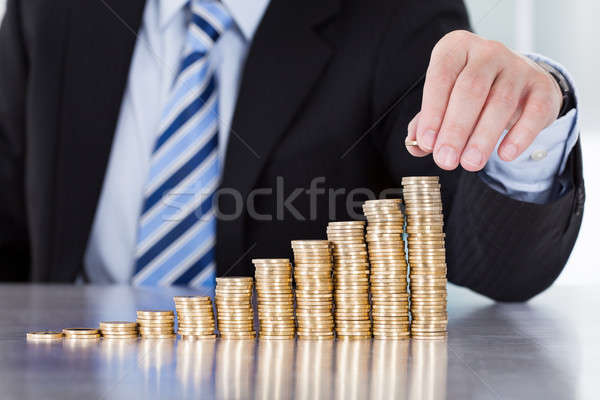 Close-up Of Businessman Hand Put Coins To Stack Of Coins Stock photo © AndreyPopov