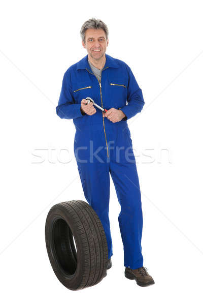 Automechanic standing next to car tire Stock photo © AndreyPopov