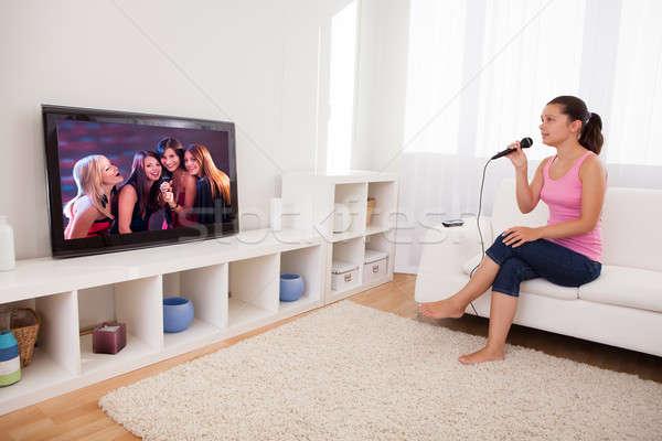 Młoda kobieta śpiewu karaoke mikrofon patrząc telewizji Zdjęcia stock © AndreyPopov