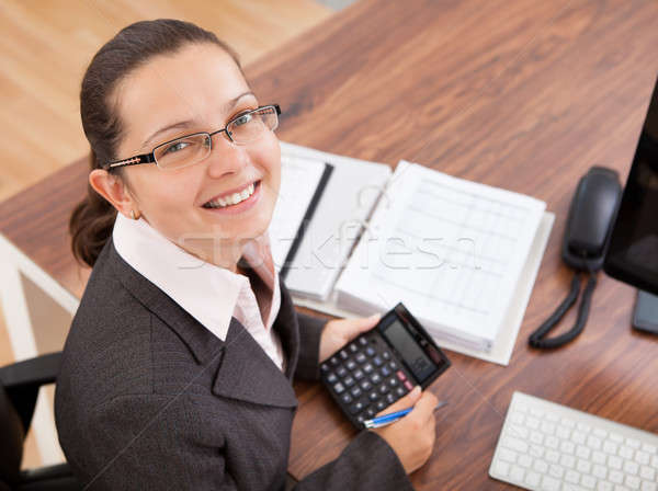Happy young woman calculating finances Stock photo © AndreyPopov