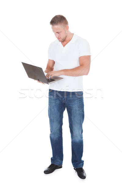 Smiling man using a handheld laptop computer Stock photo © AndreyPopov