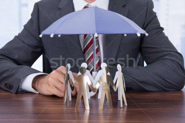 Businessman Sheltering Paper People With Umbrella Stock photo © AndreyPopov