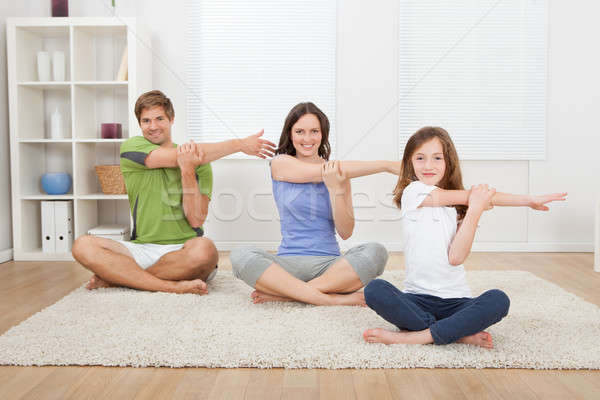 Smiling Family Performing Yoga On Rug Stock photo © AndreyPopov